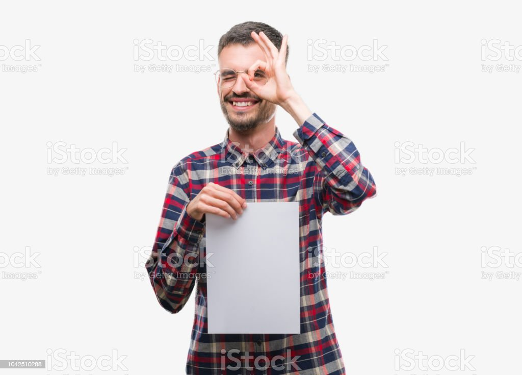Young hipster adult man holding blank paper sheet with happy face smiling doing ok sign with hand on eye looking through fingers stock photo