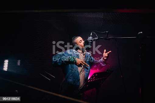 Young fashionable hip hop singer singing and recording music in professional music recording studio