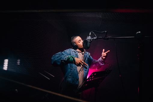 Young hipster African-American rapper recording songs in music recording studio