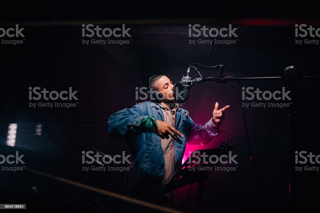 Young hipster African-American rapper recording songs in music recording studio stock photo