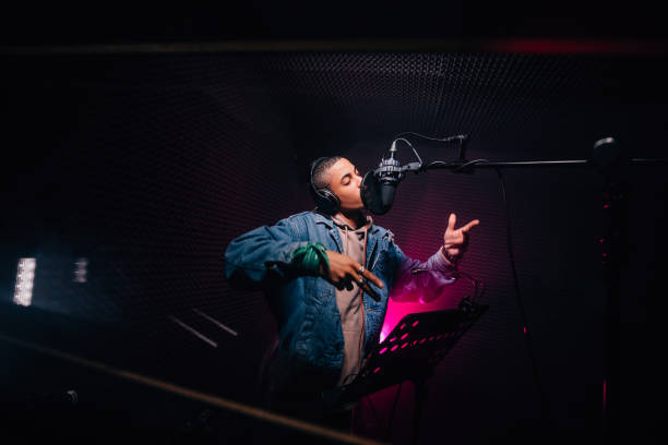 Young hipster African-American rapper recording songs in music recording studio Young fashionable hip hop singer singing and recording music in professional music recording studio singer stock pictures, royalty-free photos & images