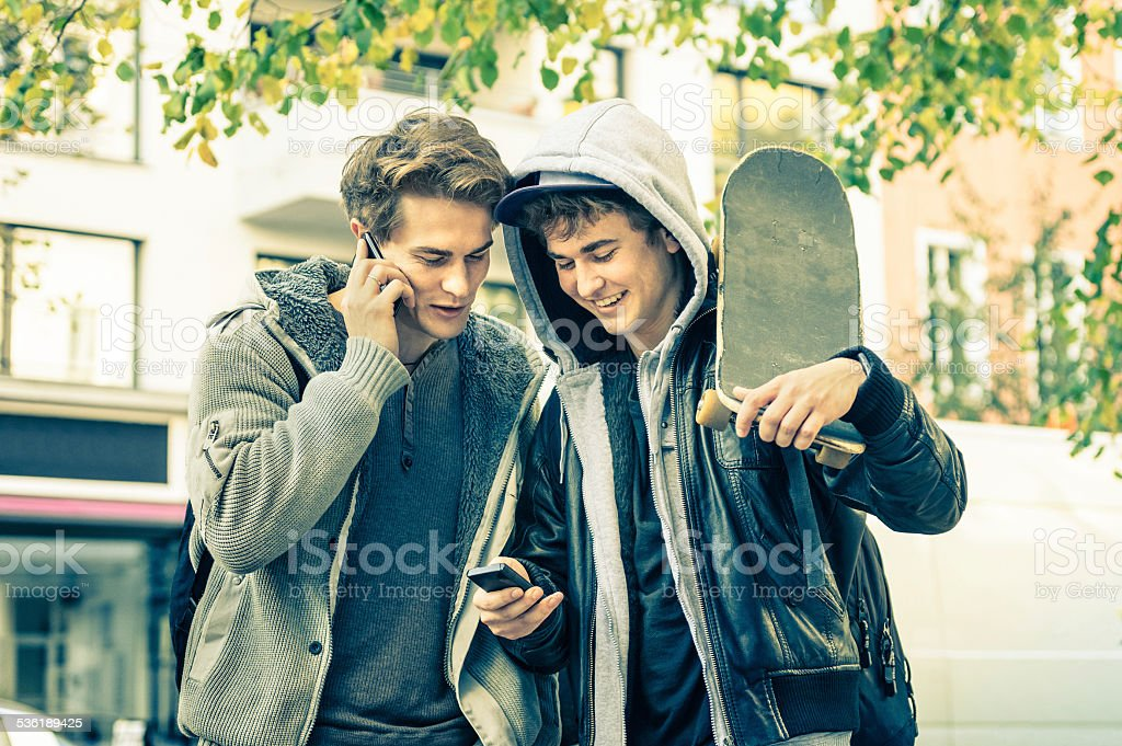 Young hipster best friends brothers having fun with smartphone stock photo