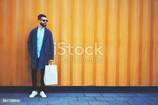 istock Young hipster blogger traveler in a denim jacket holding bag with copy space for your brand name 694188640