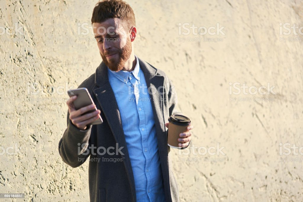 Young hipster blogger traveler in a denim jacket using navigator application on smartphone connected to fast 4G internet - foto stock