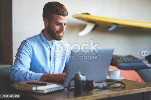 904263506 istock photo Young hipster blogger traveler while keyboarding on laptop computer connected to 5G wireless 694168284