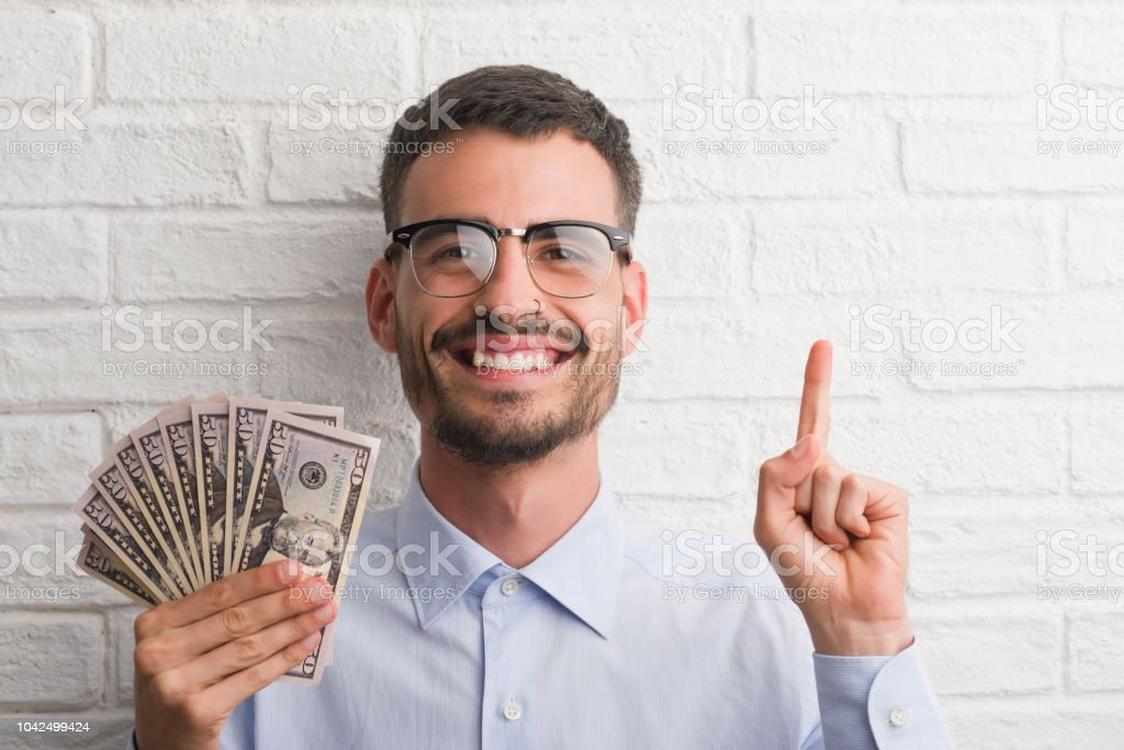 Young hipster business man holding dollars surprised with an idea or question pointing finger with happy face, number one royalty-free stock photo