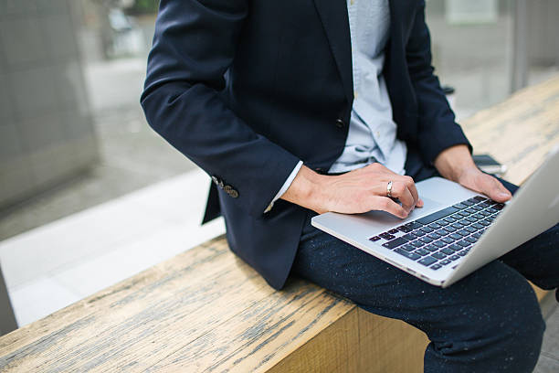 Young hipster businessman in suit typing laptop near office outd – Foto