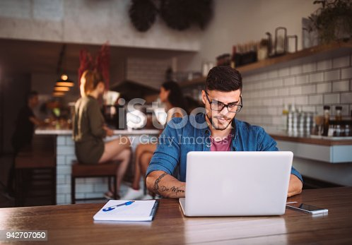 istock Young hipster businessman working on laptop at urban coffee shop 942707050