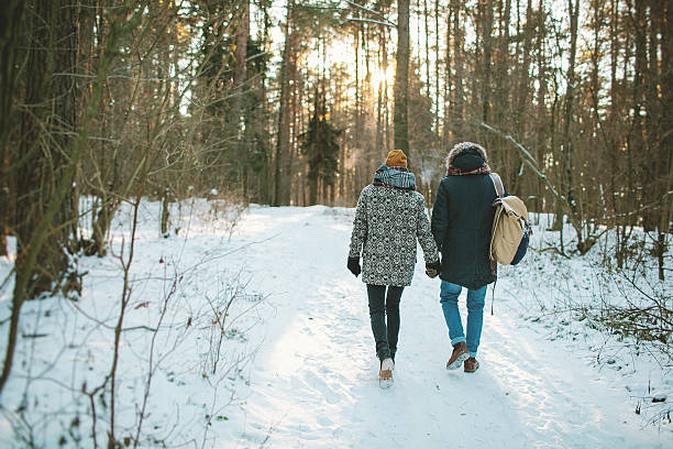 Young hipster couple having a walk in winter forest stock photo