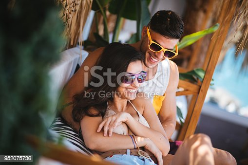 Young hipster couple on summer holidays relaxing and having fun at island summer beach bar