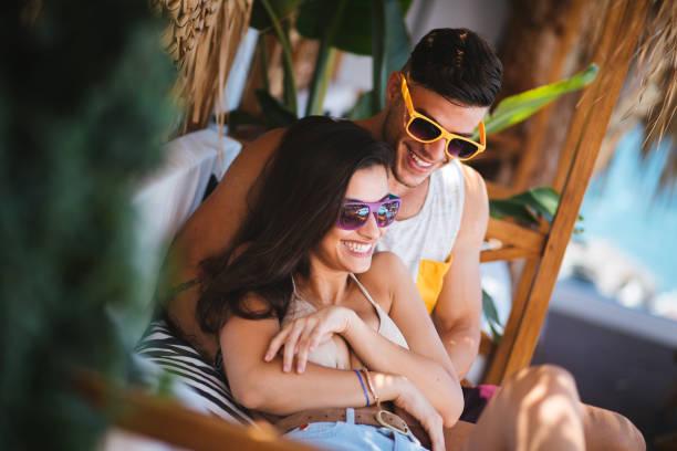 junge hipster-paare, die spaß am sommer-strand-café - hochzeitsreise ohne mann stock-fotos und bilder
