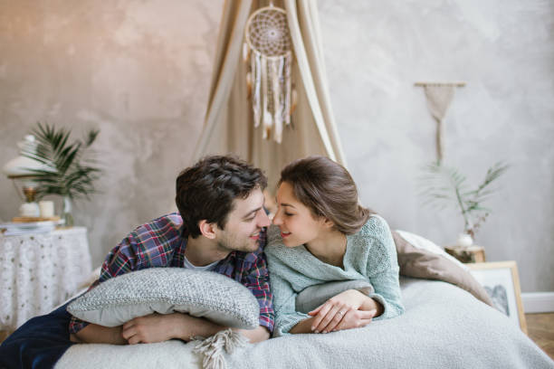 Young hipster couple having fun on handmade bed with dreamcatcher stock photo