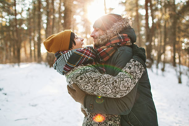 Young hipster couple hugging each other in winter forest stock photo