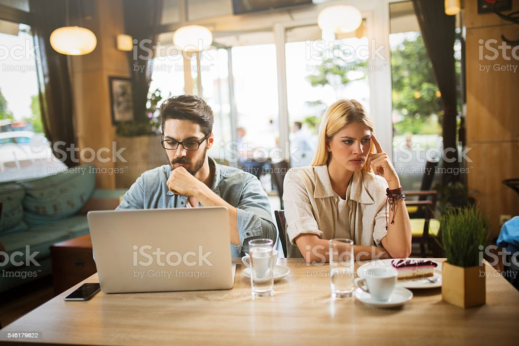 Young hipster couple in moment of mutual disinterest and sadness. stock photo