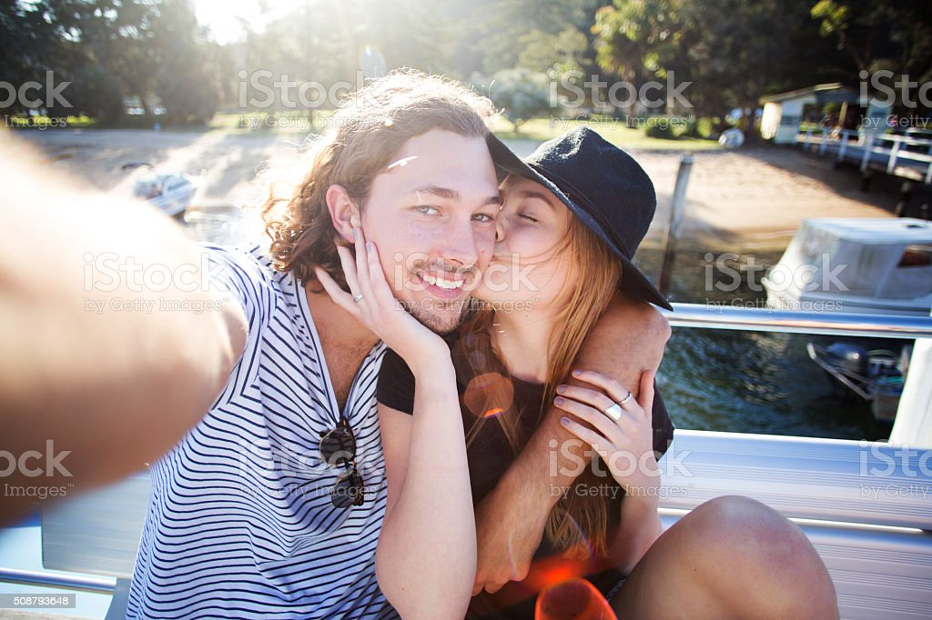 Young hipster couple kissing on boat taking selfie stock photo
