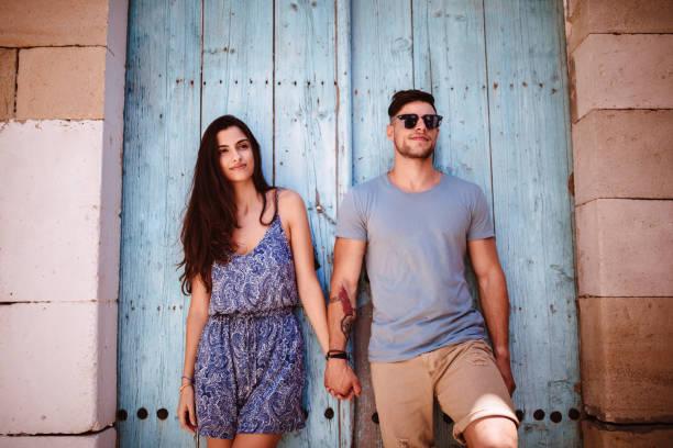 junge hipster paar an feiertagen gegen alte blaue tür - hochzeitsreise zypern stock-fotos und bilder