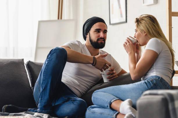Junge Hipster-Paar sitzt auf dem Sofa zu Hause reden und Kaffee trinken – Foto