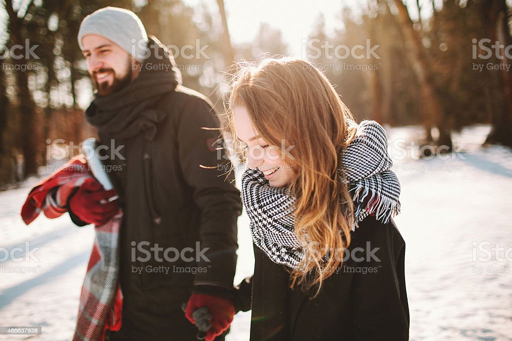 Young hipster couple walking in winter forest holding hands stock photo