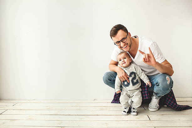 Young hipster father and baby boy on wooden floor stock photo