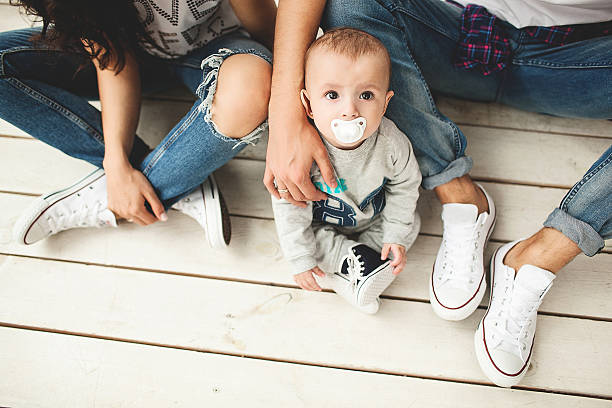 Young hipster father, mother and baby boy on wooden floor stock photo