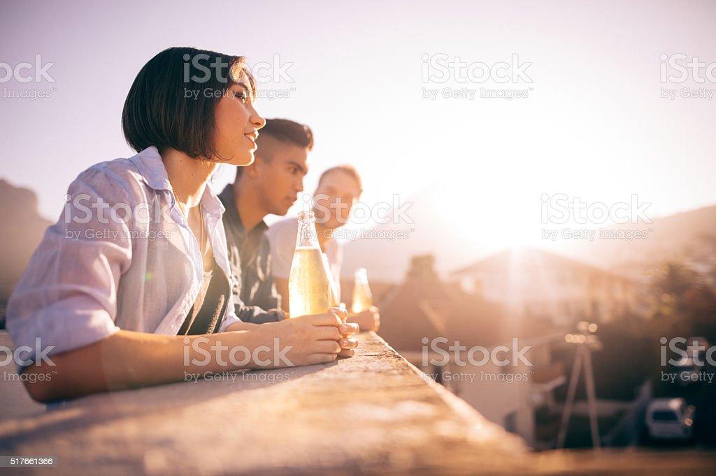 Junge Hipster Freunde trinken Bier und reden auf dem Dach – Foto
