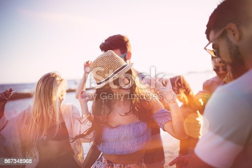Young hipster friends having fun and dancing at summer island beach party at sunset