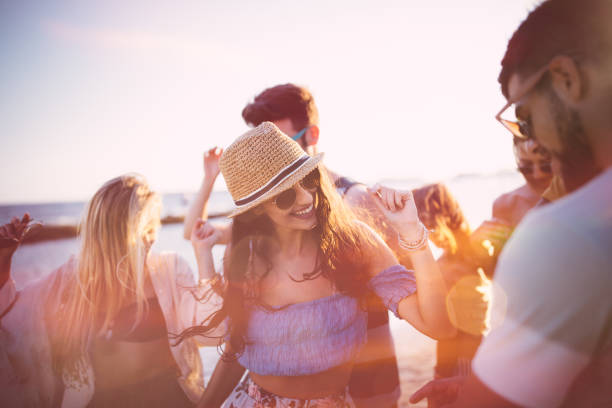 Young hipster friends on summer holidays dancing at beach party stock photo
