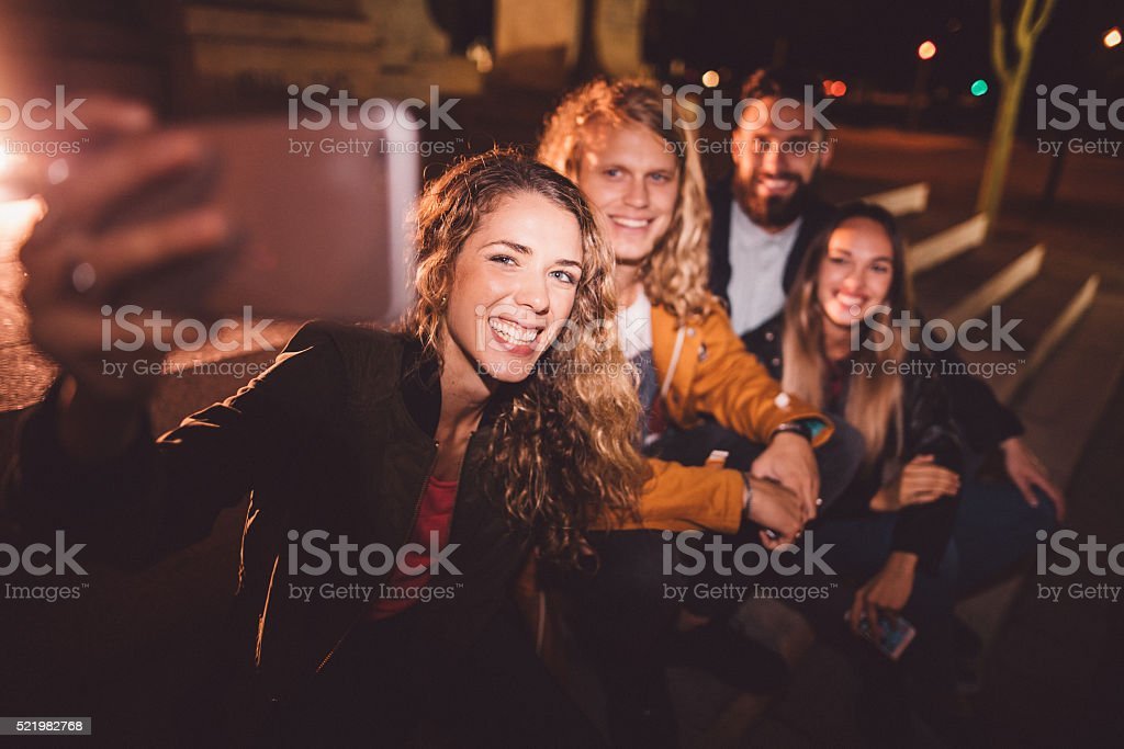 Young Hipster friends taking selfie at night in town stock photo
