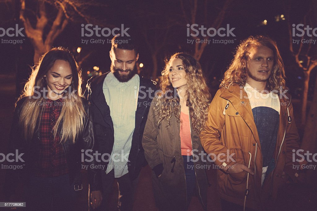 Young hipster friends walking in town on evening stock photo