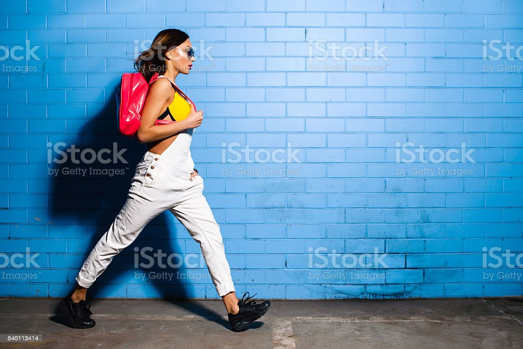 Young hipster girl posing near blue wall background in sunglasses stock photo