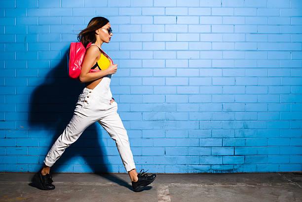 junge hipster mädchen posiert in der nähe von blaue wand hintergrund in sonnenbrille - jumpsuit blau stock-fotos und bilder