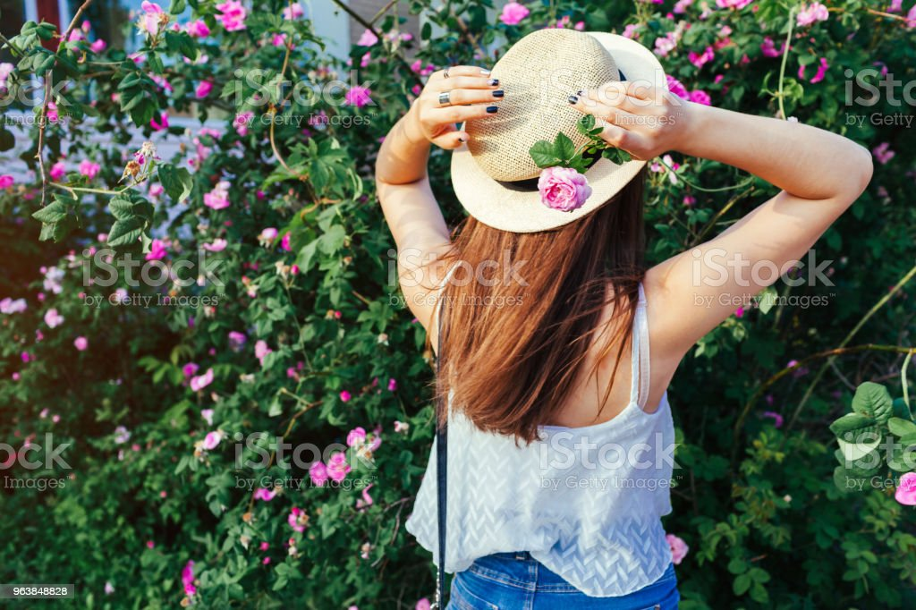 Young hipster girl wearing hat walking by blooming roses. Woman enjoys flowers in park. Summer outfit. - Royalty-free Adult Stock Photo