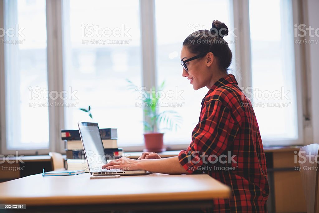Young hipster girl working on laptop stock photo