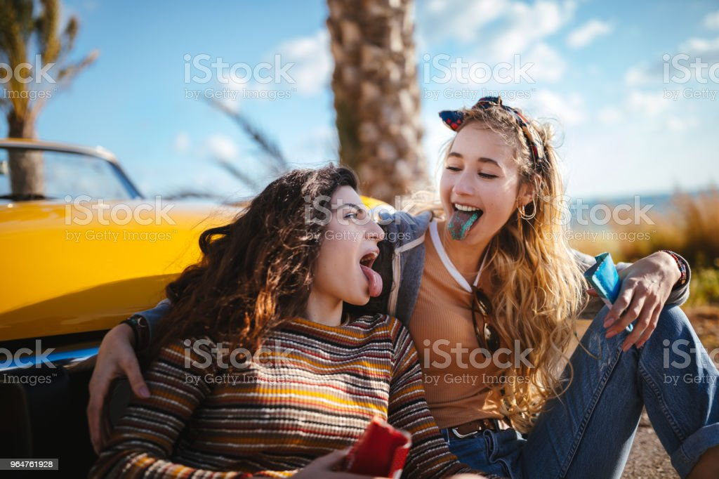Young hipster girls eating candy on tropical island road trip royalty-free stock photo