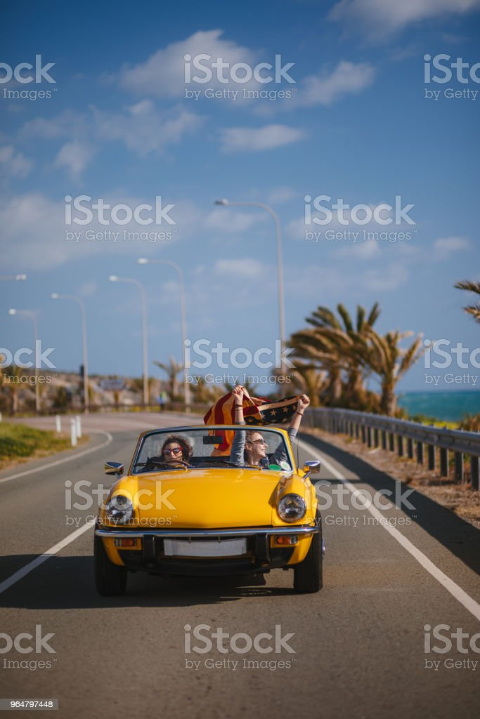 Young hipster girls with American flag driving vintage convertible car royalty-free stock photo