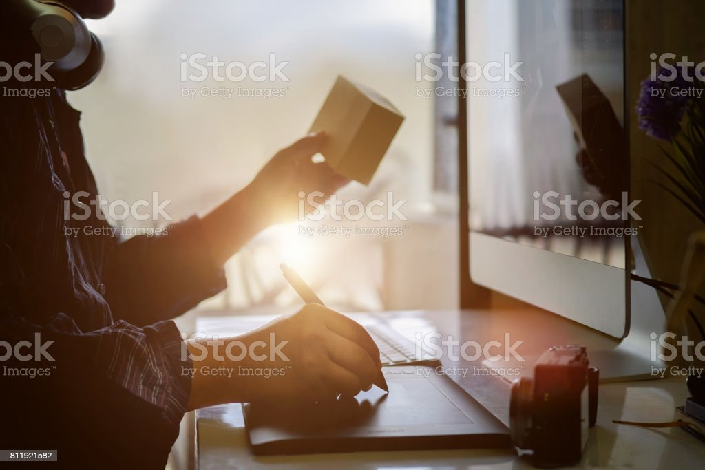 Young hipster graphic designer man using digital graphic tablet while working at modern office stock photo