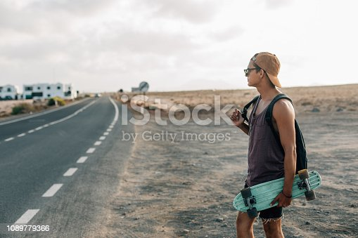 Young hipster guy with skateboard and backpack, standing on a asphalt roadside.