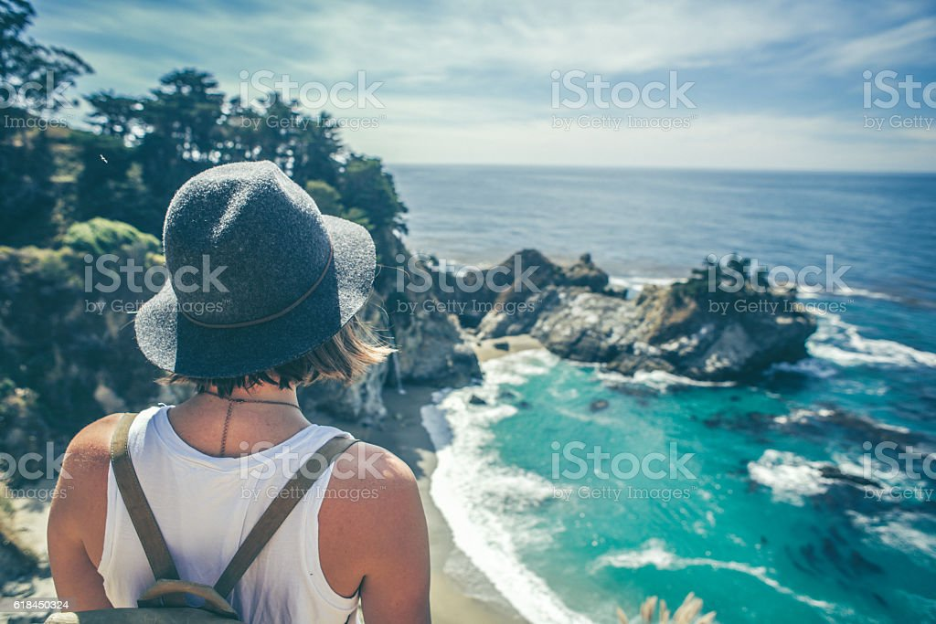 Young hipster looking out over the beach stock photo