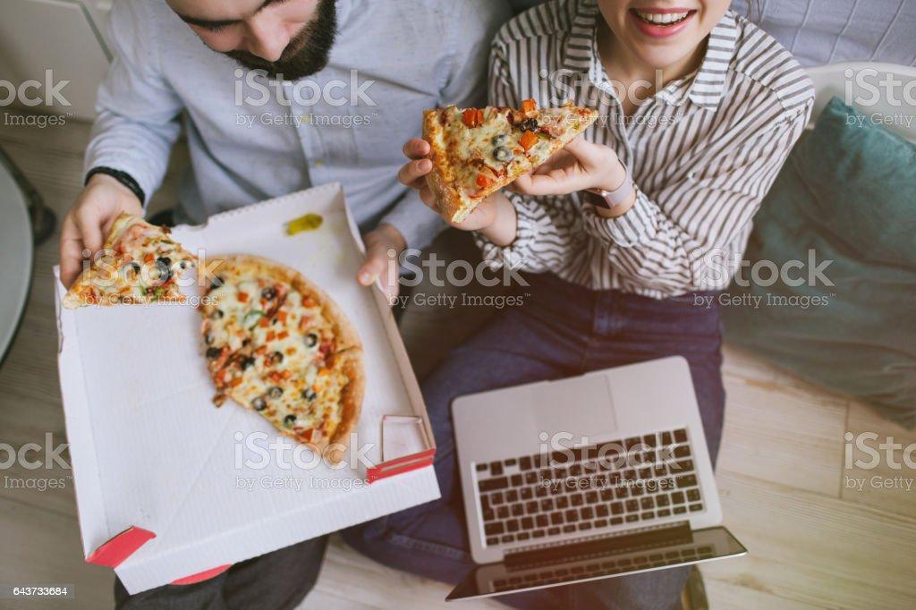 Couple femelle mâle hipster jeune maison manger pizza avec ordinateur portable - Photo