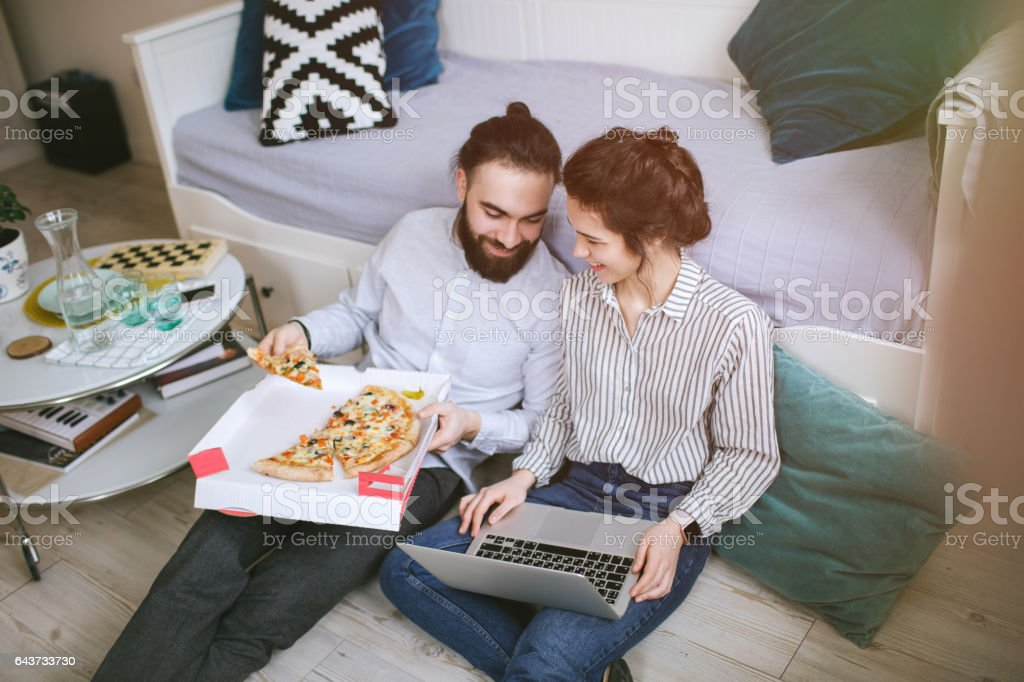 Young hipster male female couple home eating pizza with laptop – Foto