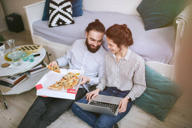 Young hipster male female couple home eating pizza with laptop stock photo