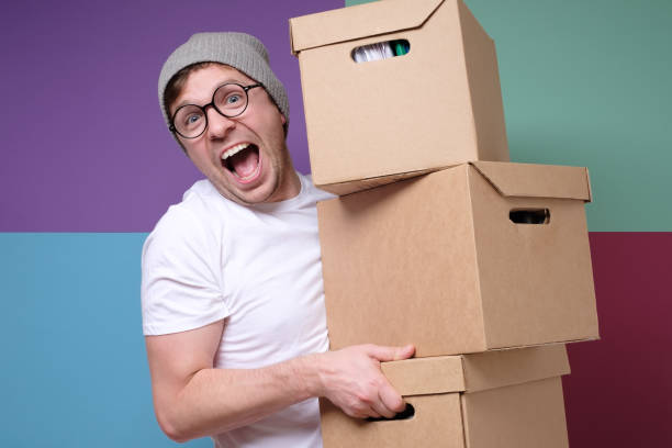 Young hipster man in hat and glasses carrying paper boxes isolated on colored background stock photo
