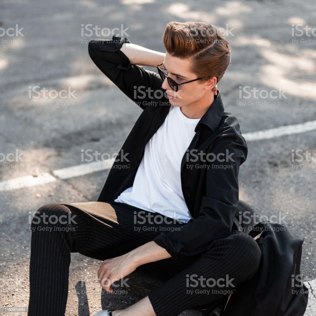 Joven Hipster Hombre En Camisa De Moda En Pantalones Con Mochila Con Peinado Posesiones Sentado En El Asfalto En La Ciudad En Un Dia Soleado De Verano Brillante Guapo Tipo Hipster Con