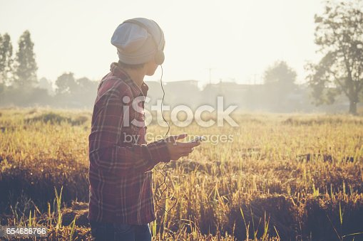 istock young hipster Man listening to music, mobile phone, headphones, enjoying on time 654686766