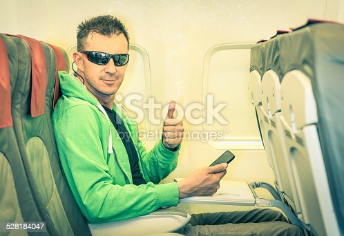 istock Young hipster man passenger satisfied with thumbs up inside airplane 528184047