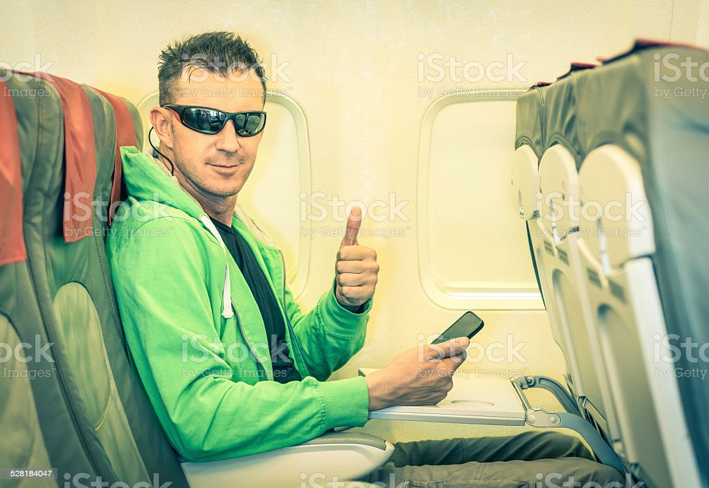 Young hipster man passenger satisfied with thumbs up inside airplane stock photo
