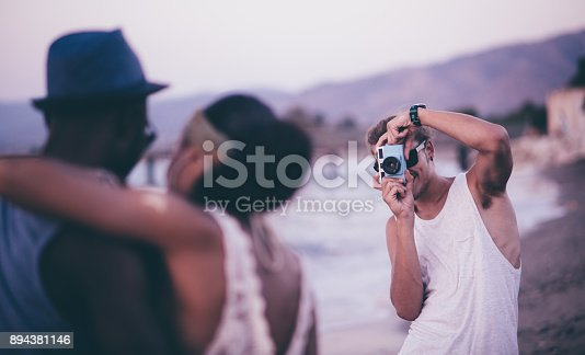 istock Young hipster man photographing friends with vintage camera at beach 894381146