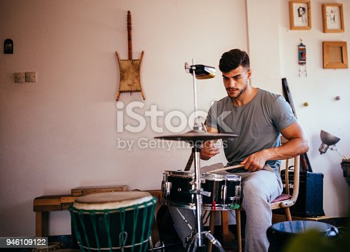 Handsome young drummer musician holding drumsticks and playing the drums rehearsing for his music band