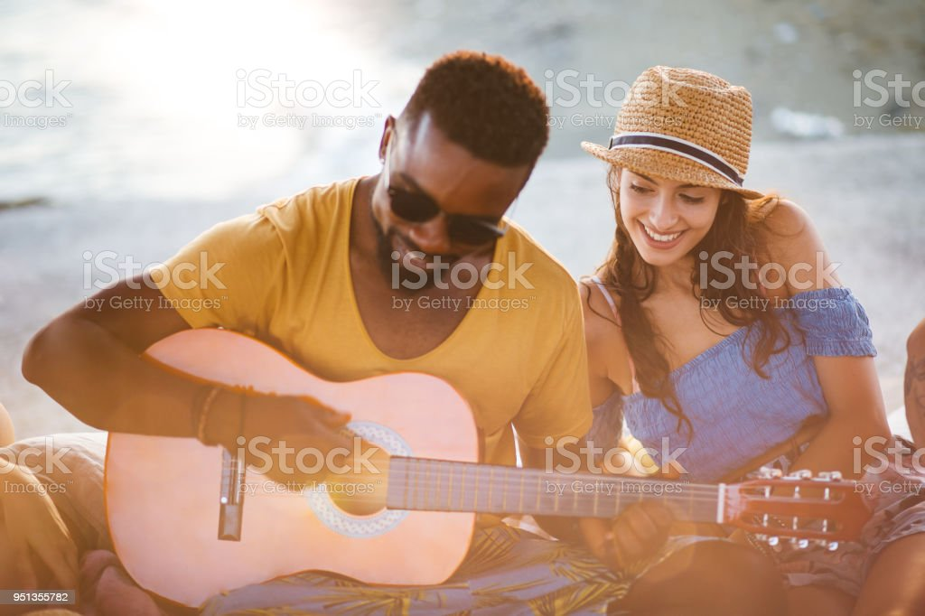 Young hipster man playing the guitar at summer beach party stock photo