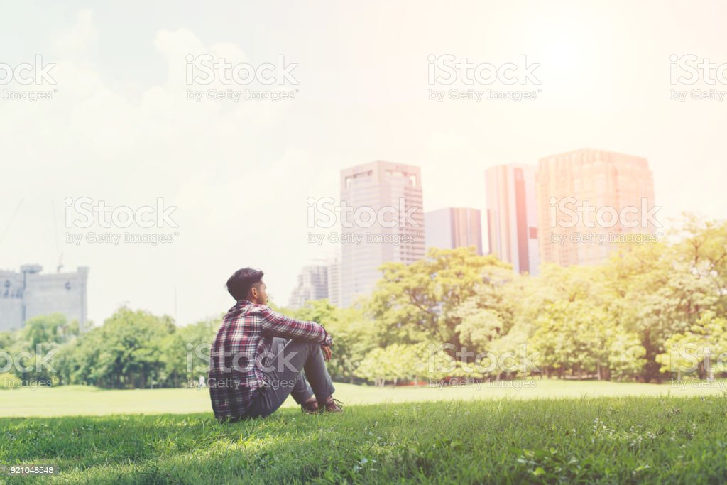 Young hipster man sitting on grass in the park alone against the city and sky. stock photo